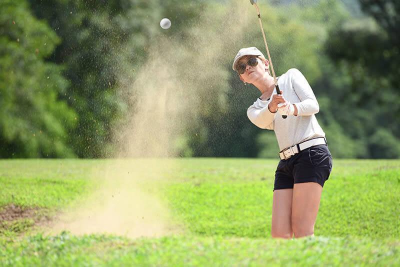 Golfspielerin pitcht einen Golfball