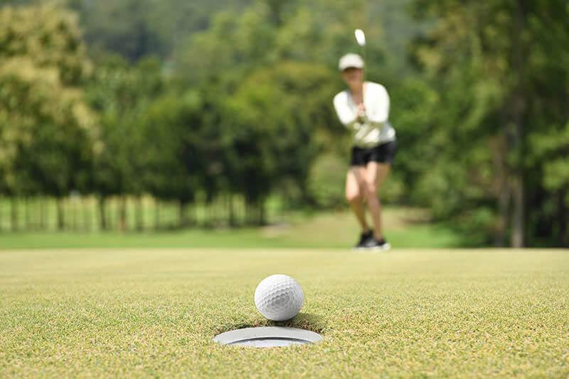 Golfspielerin locht ein