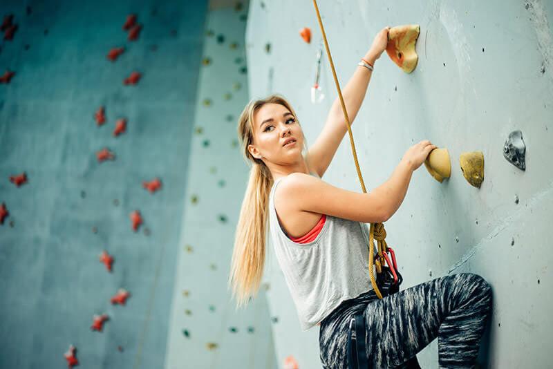 Frau klettert an einer Kletterwand